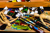 An artist's painting tools ready to be used in the studio.  Brushes and model figurines round out the fine art tools used by a painter.