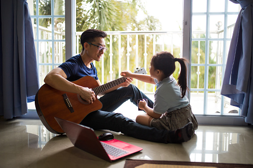 An Asia Chinese businessman work from home. Playing Guitar during coffee break time. Daughter sitting beside and spending wonderful time with him