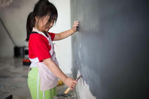 An Asia Chinese girl is helping family scraping the peel off part at the wall preparing for painting