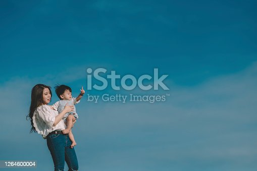 an asia chinese young mother having a morning walk at her residential public park with her baby boy