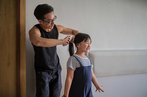 An Asia mature father tie up daughter hair ready for installing furniture.