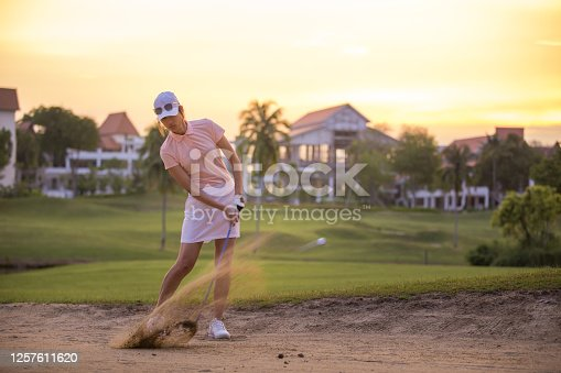 istock An Asia mature golfer hit the ball in the sand. 1257611620