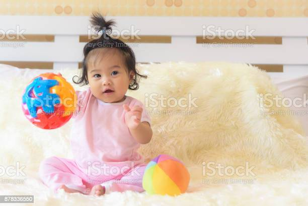 An asian baby girl is playing in her bed with a happy expression picture id878336550?b=1&k=6&m=878336550&s=612x612&h=xl 2thqccmr5ds59pu9bcqyg9jo75eqvr3qrkxeo hg=