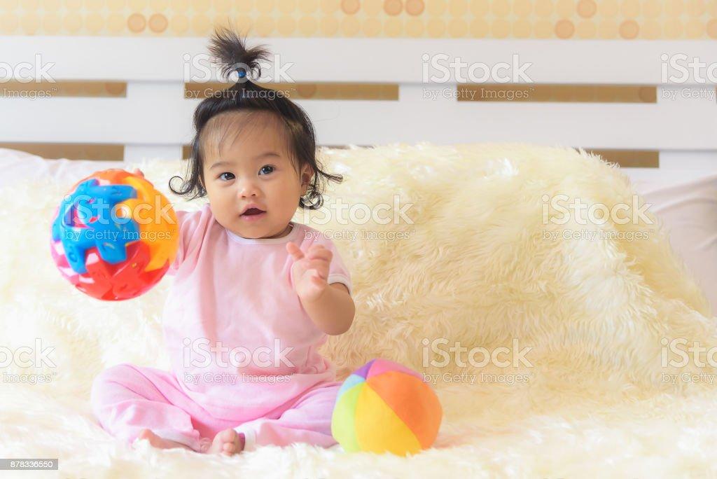 Eine asiatisches Babymädchen spielt in ihrem Bett mit einem glücklichen Ausdruck. – Foto