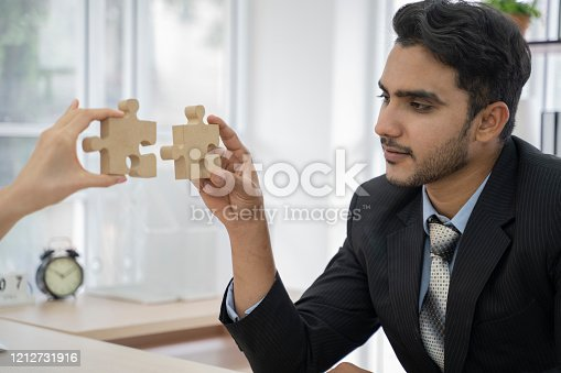 639198068 istock photo An asian business people sitting at office desk, putting puzzle pieces together, finding solution. 1212731916