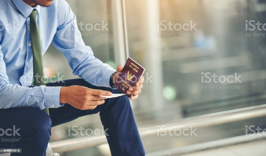 An Asian businessman is holding a plane ticket and his passport is waiting to depart.Focus on hand holding ticket. stock photo