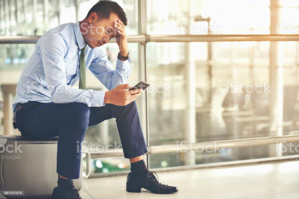 Ein asiatische Geschäftsmann sitzt auf seinem Gepäck. Er war gestresst und schaute auf sein Smartphone am Flughafen. – Foto