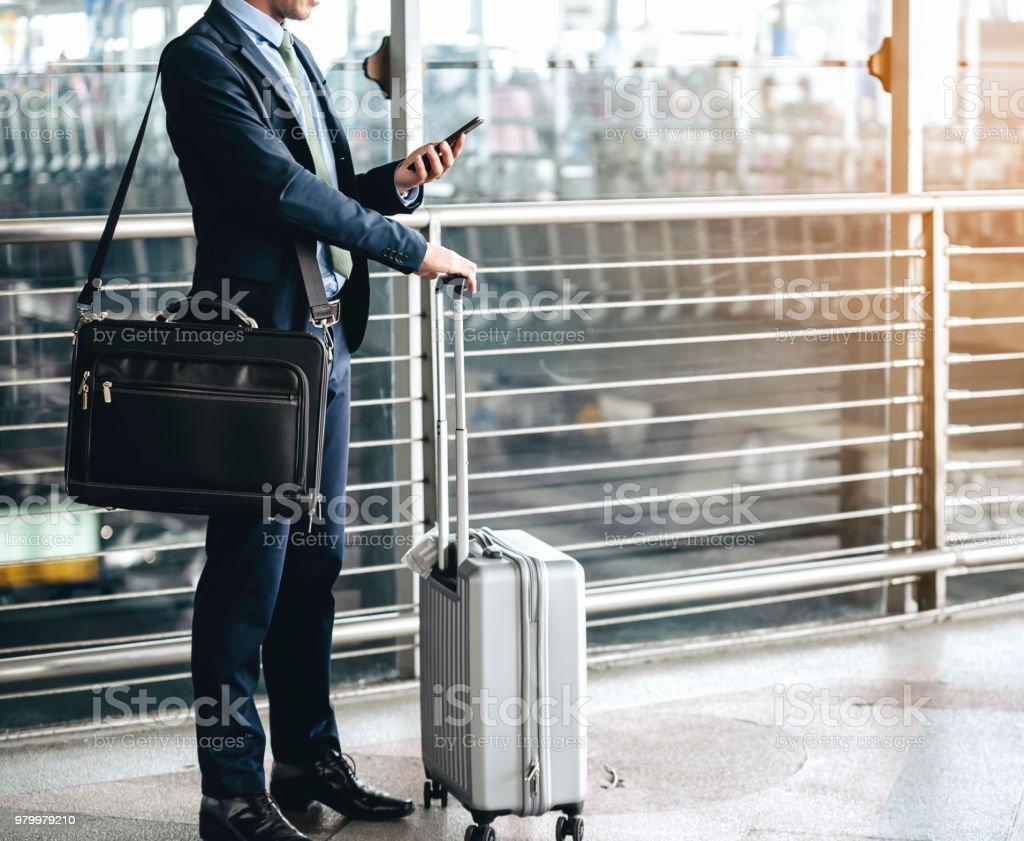 Ein asiatische Geschäftsmann nutzt eine Smartphone, um im Geschäft zu bekommen, während des Wartens auf eine Reise in den Flughafen. – Foto