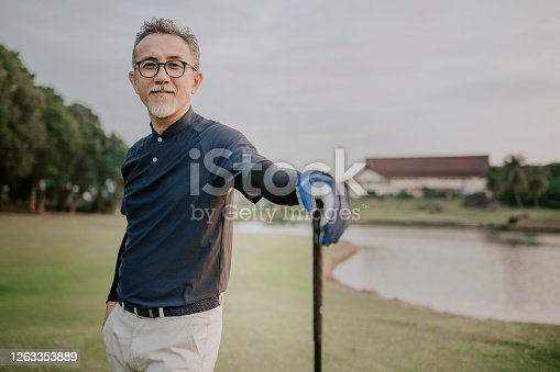 an asian chinese active senior man golfer standing with his golf club driver in the golf course after the golf game waiting and looking