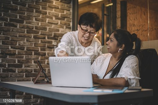 926404274 istock photo an asian chinese active senior woman guiding her colleague on the office work using laptop 1210297658