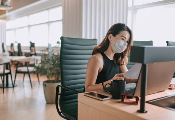 an asian chinese beautiful woman white collar worker working in coworking office with face mask on for illness prevention - new normal foto e immagini stock