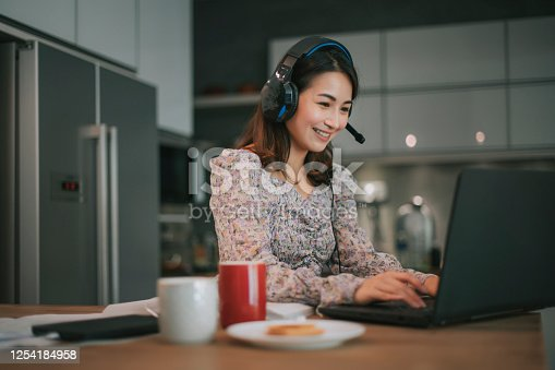 an asian chinese beautiful woman working from home as customer service answering to her customer online using laptop and headphone in the kitchen typing