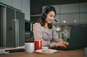 istock an asian chinese beautiful woman working from home as customer service answering to her customer online using laptop and headphone in the kitchen typing 1254184958