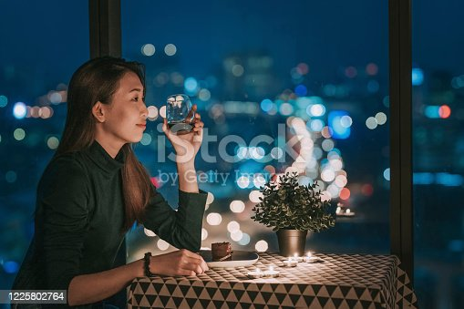 an asian chinese beautiful young lady having dessert in her apartment during magic hour, dusk relaxing and enjoying moment