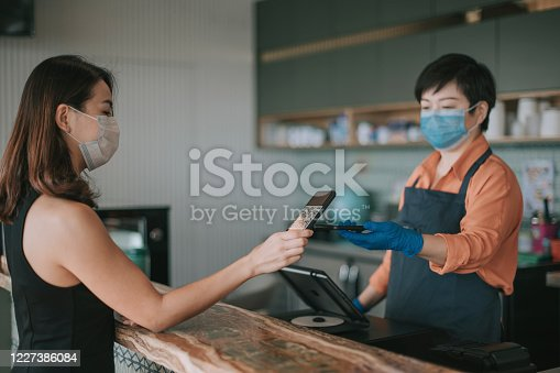 an asian chinese cafe owner businesswoman receiving payment from her customer at counter using QR code contactless payment