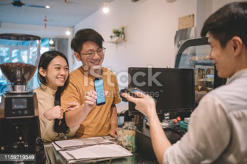 istock an asian chinese couple making contactless payment with smartphone at cafe 1159219349