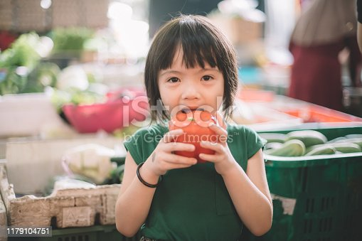 an asian chinese cute child looking at camera holding a red pepper in the market