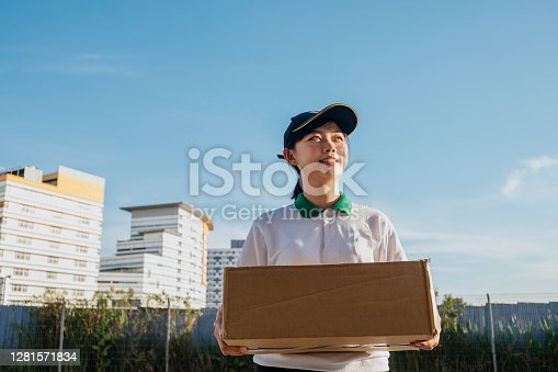 An Asian Chinese delivery woman holding a cardboard box and delivering goods to online shopping customer