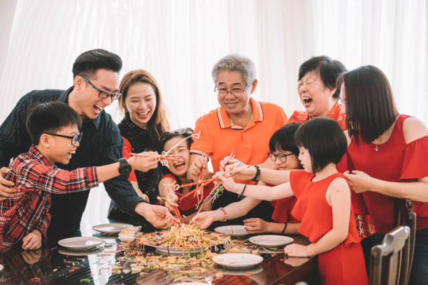 an asian chinese family celebrating chinese new year's eve with traditional food Lou sang (raw fish dishes) during reunion dinner stock photo