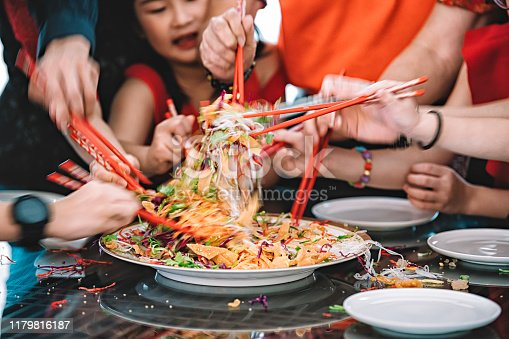an asian chinese family celebrating chinese new year's eve with traditional food Lou sang (raw fish dishes) during reunion dinner