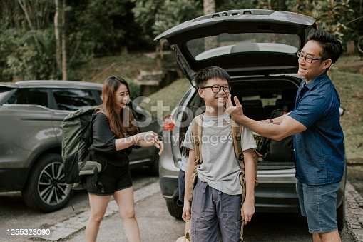 an asian chinese father getting ready for hiking packing from his car boot with his family