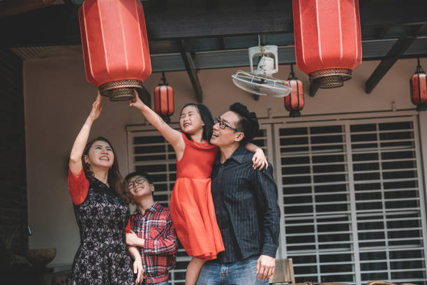 an asian chinese family in malaysia fixing their red lanterns for chinese new year preparation in front of their house stock photo