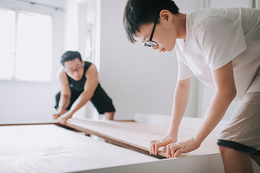 an asian chinese family moving house father and son assemble bed frame