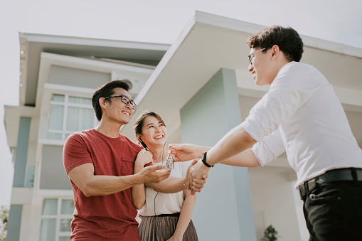 an asian chinese family moving into new house and received the house key from real estate agent