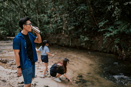 an asian chinese family of 1 child standing in front of the tropical rainforest in the morning enjoying at river side