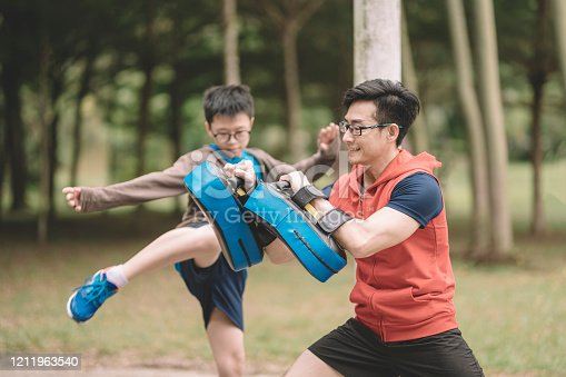 an asian chinese father athlete training his 12 years son in the public park in the evening