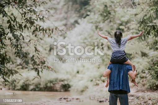 an asian chinese father carrying his daughter on shoulder in the jungle enjoying bonding time together at the river during weekend leisure time