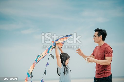 an asian chinese father playing and flying kite with his daughter at the beach