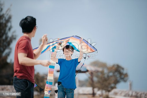an asian chinese father playing and flying kite with his son at the beach