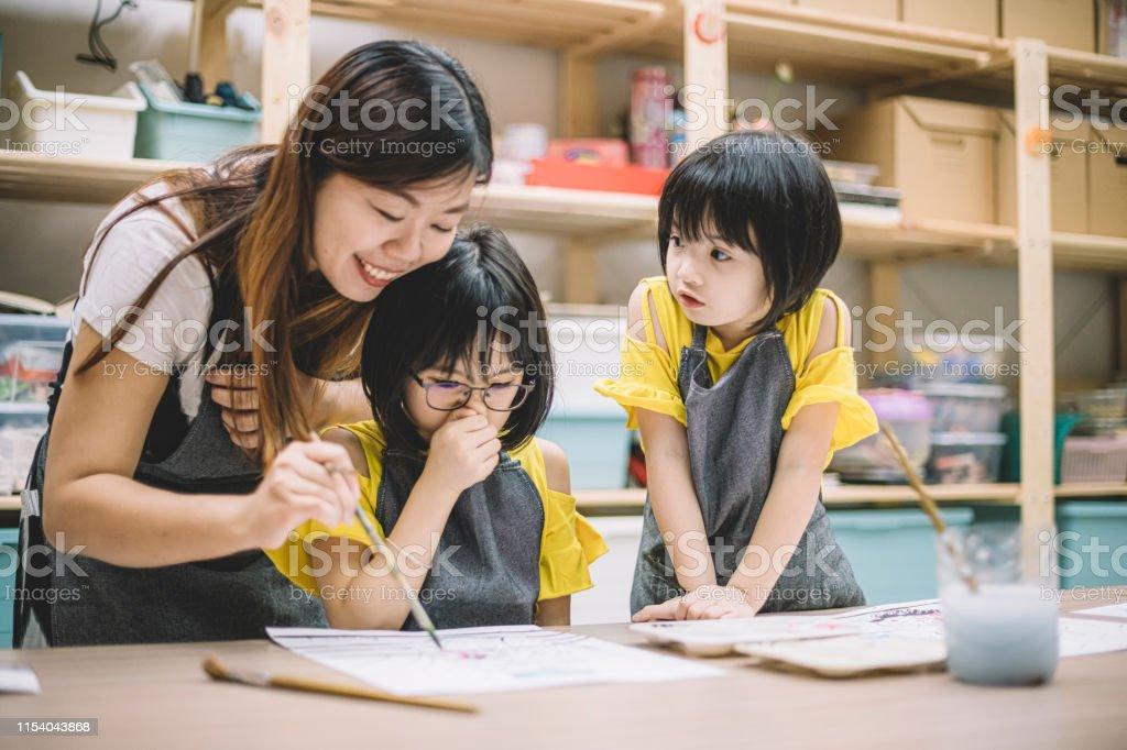 un professeur asiatique de classe d'art chinoise enseignant ses 2 étudiants de classe d'art sur le dessin dans sa classe d'art - Photo de Activité de loisirs libre de droits