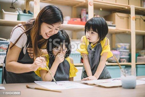 istock an asian chinese female art class teacher teaching her 2 art class students on drawing in her art class 1154043868