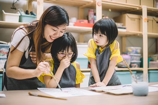An Asian Chinese Female Art Class Teacher Teaching Her 2 Art Class Students On Drawing In Her Art Class Stock Photo - Download Image Now