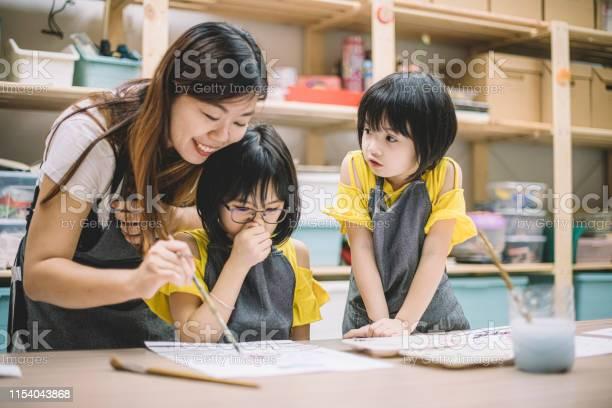 Photo libre de droit de Un Professeur Asiatique De Classe Dart Chinoise Enseignant Ses 2 Étudiants De Classe Dart Sur Le Dessin Dans Sa Classe Dart banque d'images et plus d'images libres de droit de Activité de loisirs