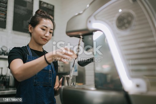 An asian chinese female barista making coffee with coffee machine at the cafe