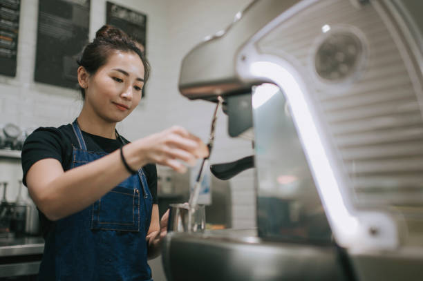 An asian chinese female barista making coffee with coffee machine at the cafe An asian chinese female barista making coffee with coffee machine at the cafe image stock pictures, royalty-free photos & images