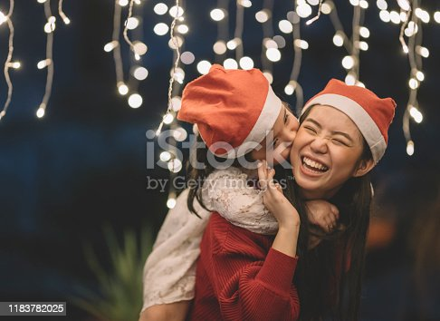 an asian chinese female carrying her sister from the back during christmas eve dinner celebration