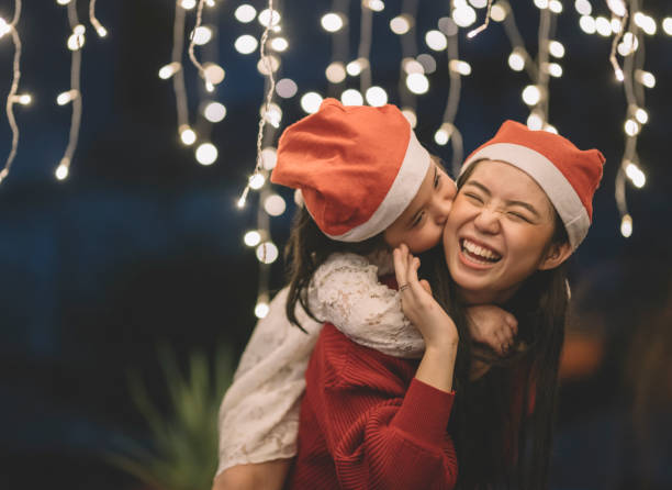 an asian chinese female carrying her sister from the back during christmas eve dinner celebration stock photo