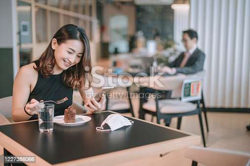 an asian chinese female enjoying her dessert chocolate cake during her tea break in cafeteria while practicing social distancing