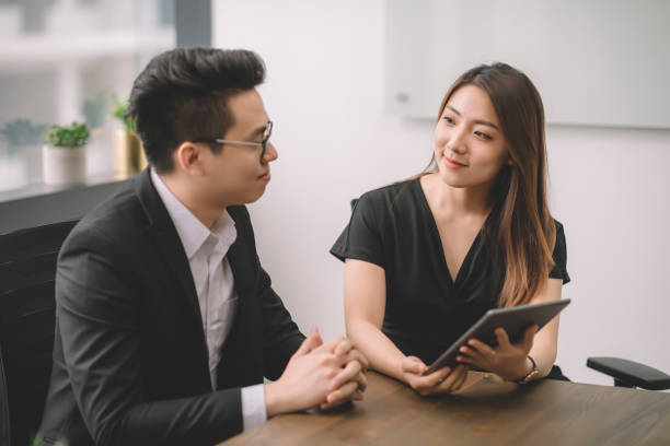 an asian chinese female explaining to her client on the business proposal in the meeting room at office stock photo