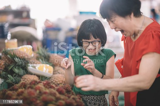 an asian chinese female grandmother bring her granddaughter to fruit market choosing pineapples and showing it to her granddaughter
