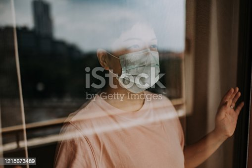 an asian chinese female looking out from her balcony window with her face mask during the restricted movement order in malaysia