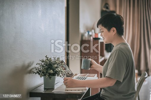 670150938 istock photo an asian chinese female mid adult working at home using her laptop and writing notes 1221345627