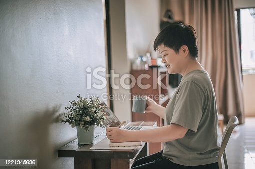 670150938 istock photo an asian chinese female mid adult working at home using her laptop and writing notes 1221345636