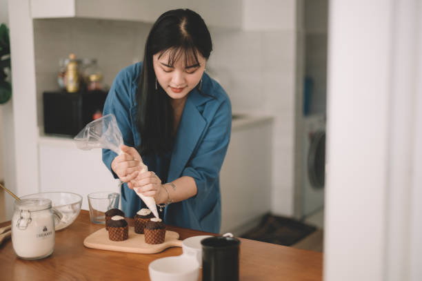 an asian chinese female piping frosting on cupcake an asian chinese female piping frosting on cupcake fondant stock pictures, royalty-free photos & images