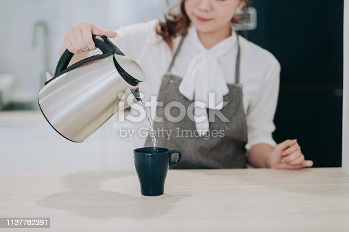 an asian chinese female pouring hot water on her coffee cup in the kitchen