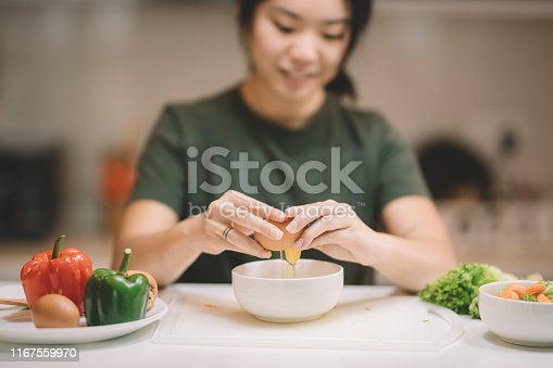 an asian chinese female preparing vegetable food salad at kitchen counter breaking eggs into bowl